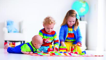 Three toddlers playing with blocks