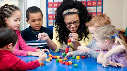 Female instructor at blue table with toddlers with string and beads