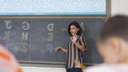 Female Instructor in striped shirt standing in front of chalk board