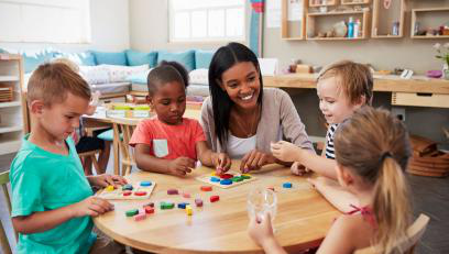 Female Instructor sitting at round table with preschoolers